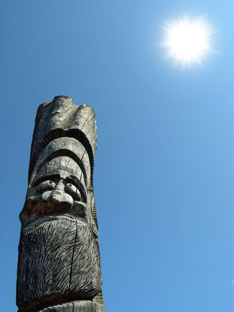 Wooden idol on the background of blue sky. A Jangseung (village guardian) is a Korean totem pole, to scare away demons. photo