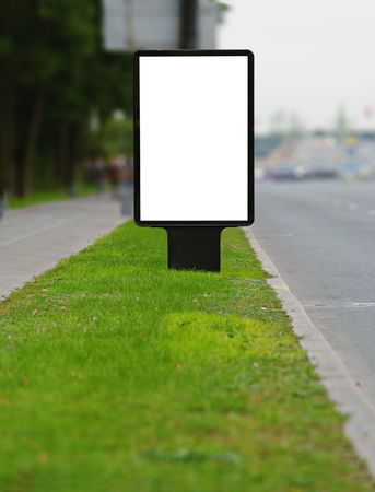 Vertical publicity board on a sward along street Stock Photo