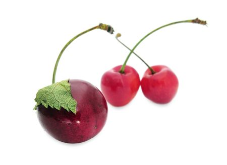 Three cherries - one with a leaf and two in the background