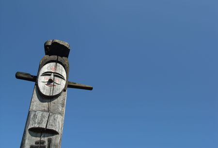 Smiling wooden idol on the background of blue sky. A Jangseung (village guardian) is a Korean totem pole, to scare away demons. photo