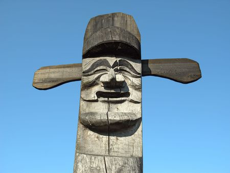 Smiling wooden idol on the background of blue sky. A Jangseung (village guardian) is a Korean totem pole, to scare away demons. Stock Photo