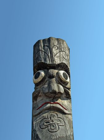 Wooden idol on the background of blue sky. A Jangseung (village guardian) is a Korean totem pole, to scare away demons.