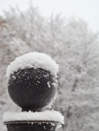 Upper part of the fence column covered with snow, close-up Stock Photo