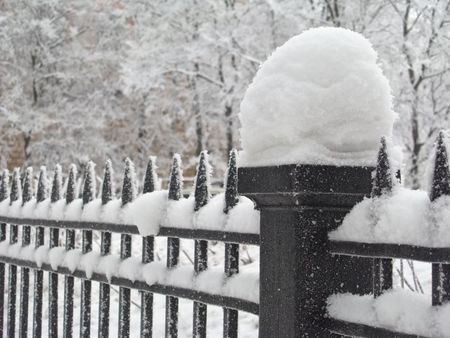 Column of the fence covered with snow, close-up