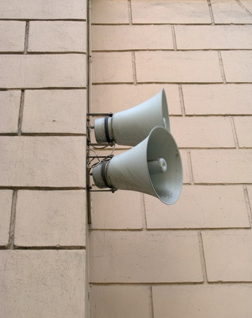 Two speakers are installed on a wall of a building
