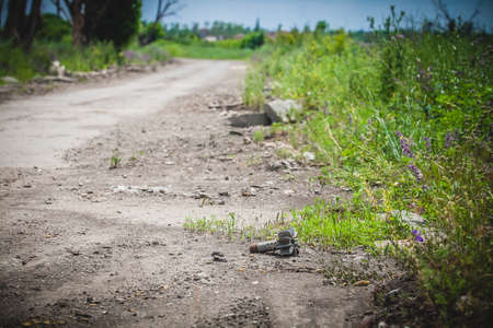 War actions aftermath, Ukraine and Donbass conflict, part of mortar shell lies on the roadside, former Airport area near city of Donetsk Reklamní fotografie