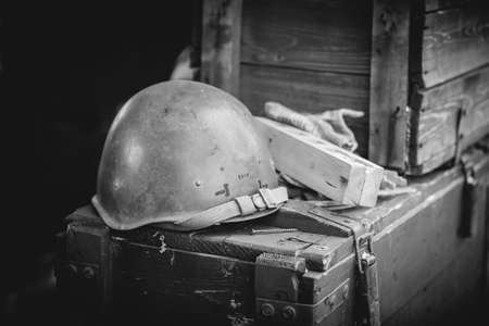 Military helmet on ammo boxes, black and white, Donbass and Ukraine military conflict, DPR soldiers trench life
