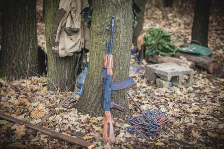 Automatic rifle leans against a tree, Donbass and Ukraine military conflict, DPR soldiers trench life Stock Photo