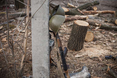 Automat, helmet and logs, Donbass and Ukraine military conflict, DPR soldiers trench life Stock Photo