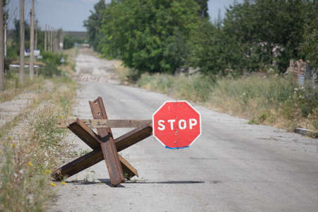 Anti-tank barrier and stop sign placed on left side of the road, Donbass and Ukraine military conflict, DPR soldiers trench life