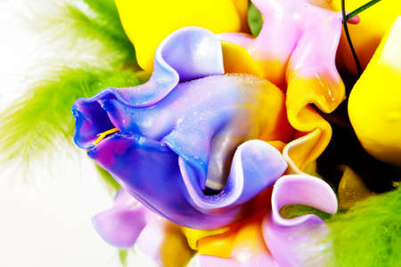 Handmade candle in the form of a bouquet of purple-yellow-blue flowers and green-yellow leaves, wax product closeup