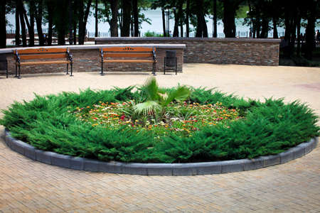 Round flower bed, benches and tiled pavement in Central Scherbakov Park of Culture and Leisure, public area