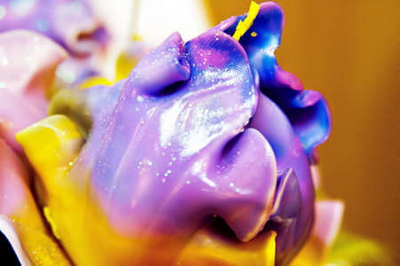 Handmade candle in the form of a bouquet of purple-blue-yellow flowers, painted wax product, one bud closeup Imagens - 112970241