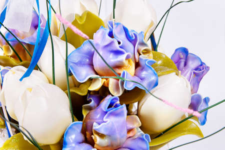 Handmade candle in the form of a bouquet of white and blue flowers and yellow leaves, pure white background, painted wax product closeup