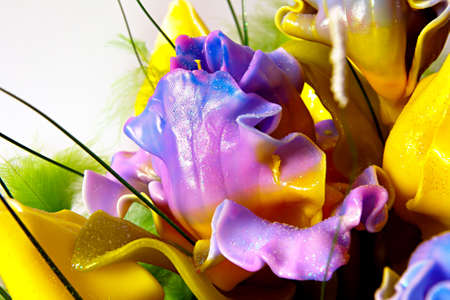 Handmade candle in the form of a bouquet of purple-blue-yellow flowers, painted wax product closeup