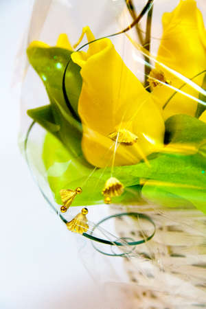 Handmade candle in the form of a bouquet of yellow tulip flowers in a wicker basket, painted wax product closeup Imagens
