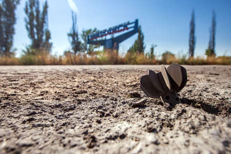 the mine shell got stuck in the road against stele with the name of the city Ilovaysk, War actions aftermath, Ukraine and Donbass conflict