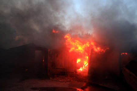a fire after a shell hit, War actions aftermath, Ukraine and Donbass conflict, burning garage 版權商用圖片
