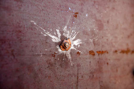War actions aftermath, Ukraine and Donbass conflict, a bullet in the metal sheet, closeup