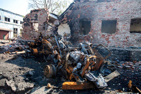 burnt military machinery in the background of the house split the pieces, War actions aftermath, Ukraine and Donbass conflict 版權商用圖片