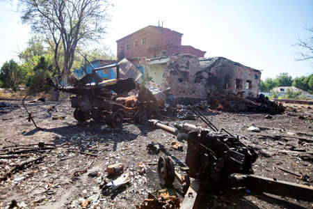 burnt military equipment and artillery gun on the background of the ruins of the house, War actions aftermath, Ukraine and Donbass conflict, shells, fragments