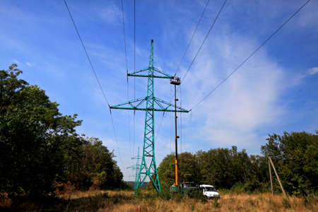 Repair works at the high-voltage power tower outside the city, minibus and maintenance truck with the elevator for high-rise works Stockfoto