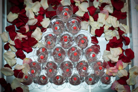 pyramid of glasses, cherry in the glass, rose petals in the background
