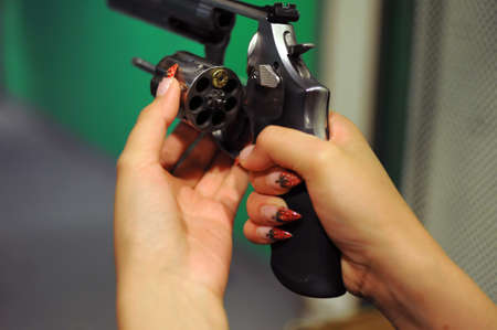 A 45 caliber revolver with ejected cylinder and one bullet in the chamber in the woman's hands with strawberry painted manicure, shot in the shooting range room Zdjęcie Seryjne