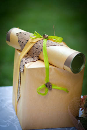 A gift packed in a gift box with a congratulatory letter and green ribbon, closeup