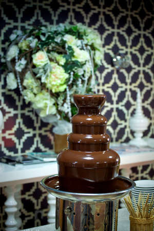 chocolate fountain on the holiday table with flower arrangement in the background