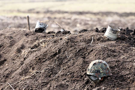 soldiers helmet of protective color lies on the ground, in the background of the shell casings of large caliber.