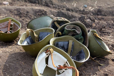 soldiers helmets lie on the ground.