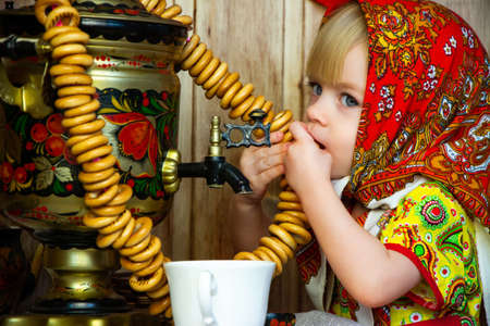 a little girl in russian folk clothes at the celebration of the slavic holiday of maslenitsa eats bagels