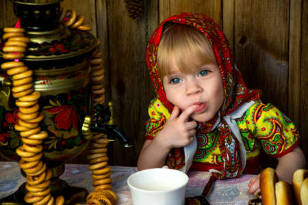 A little girl in russian folk clothes sits at a table and licks her finger, the celebration of the slavic holiday of Maslenitsa