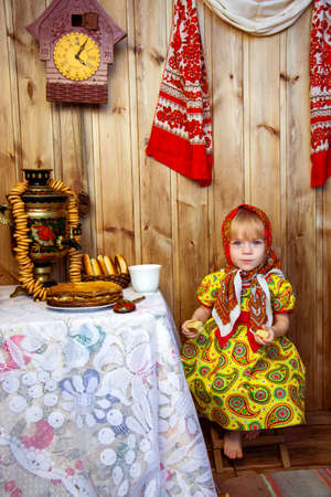a little girl in russian folk clothes at the celebration of the slavic holiday of maslenitsa eats traditional russian treats