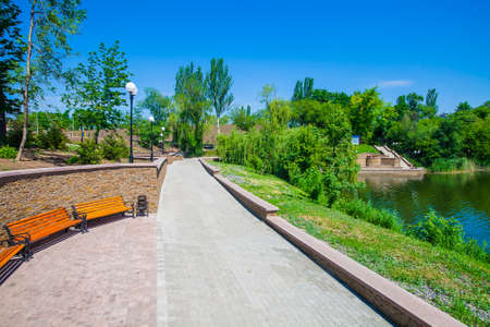Walkway and accomplishment along the coastal area near the pond in the park in the city of Donetsk