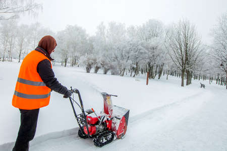 Snow removal works, a worker with snow removal equipment in action