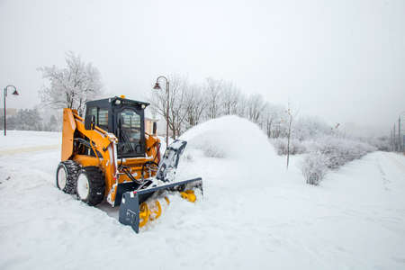 Snow removal works, snow removal tractor in action, municipal machinery