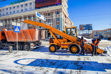 Snow removal works, snow removal tractor elevates snow in the truck with a help of two workers. Shot on Lenin Square in Donetsk, Ukraine, January 2014