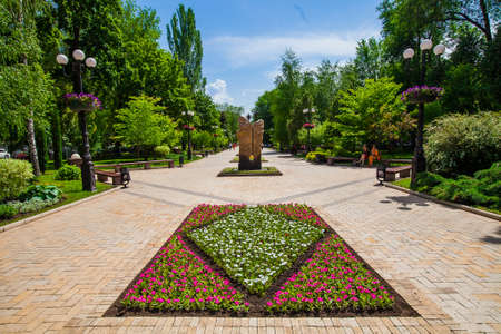 Flower bed and decorative statue in urban public place, Park infrastructure, editorial, Donetsk, Ukraine, May 2013