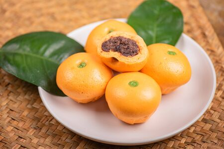 Cute pork buns in a form of oranges on white plate