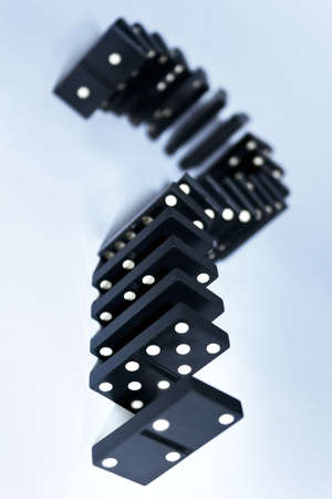 Domino pieces shaped as question sign stand still