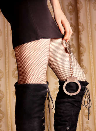 Sexy girls in stockings holds handcuffs Stock Photo