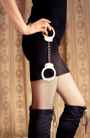 Sexy young woman in stockings holds handcuffs
