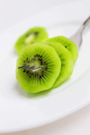 three slices of a kiwi on fork Stock Photo