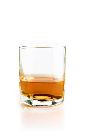 Empty glass with flowing whiskey isolated on white