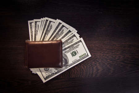 Money in a leather wallet on a dark wooden desk Stock Photo