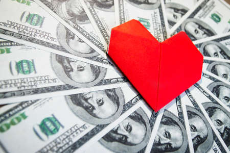 financial cash: A lot of cash US dollars and a paper heart Stock Photo
