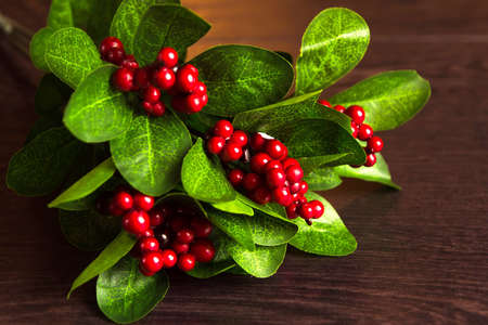 Berries red currants in an old wooden spoon. Red currant on a branch with leaves on turquoise wooden table. Stock Photo