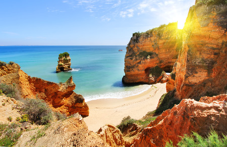 Rocky beach at sunset, Lagos, Portugal. Counter light. Travel and business background 스톡 콘텐츠